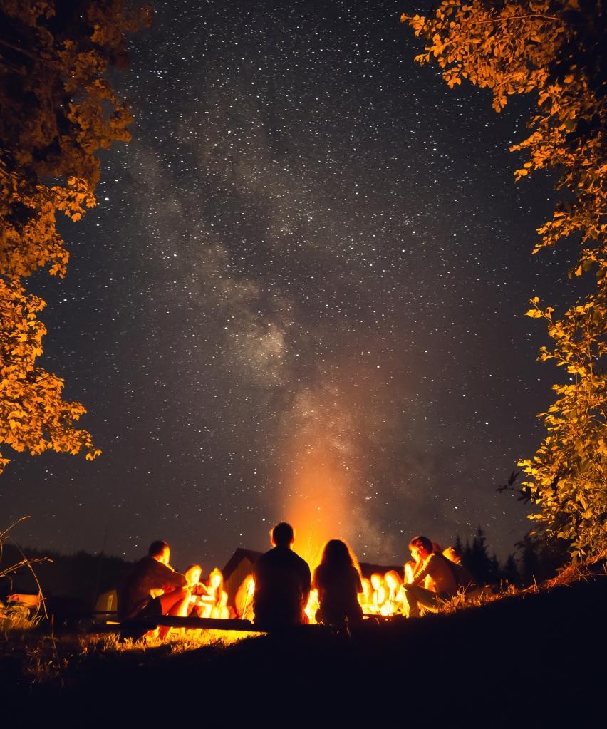 Eine Personengruppe genießt entspannt das nächtliche Lagerfeuer.