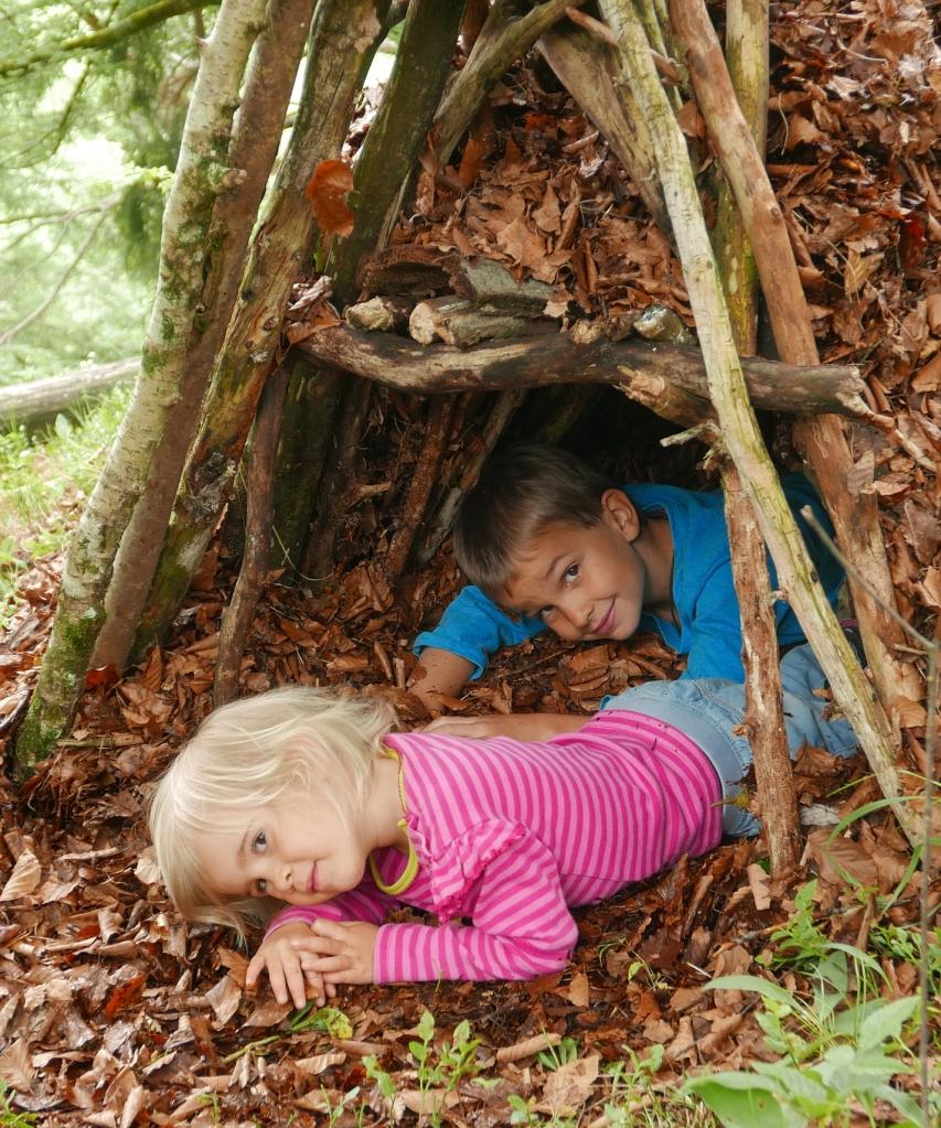 2 Kinder in einem Shelter, einer natürlichen Unterkunft aus Ästen und Laub